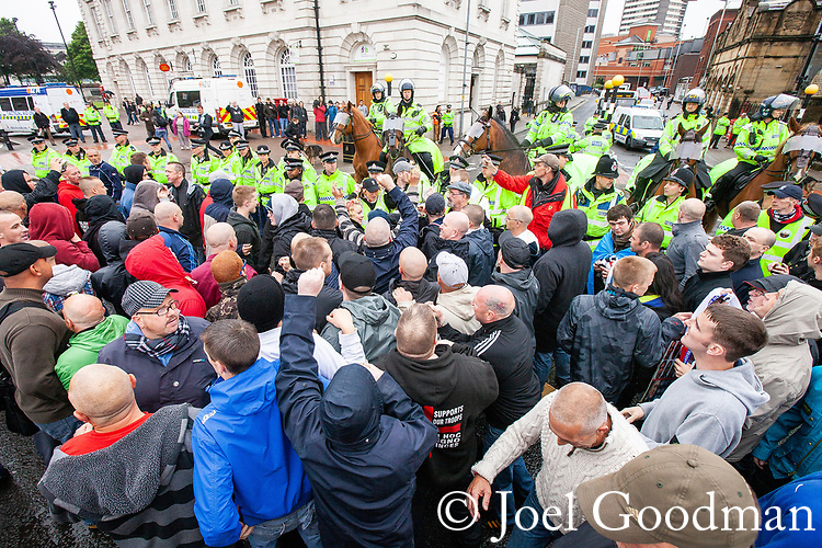 © Joel Goodman - 07973 332324 . 09/06/2012. Rochdale , UK. EDL supporters are contain by police opposite Rochdale Town Hall . The English Defence League ( EDL ) hold a march and rally in Rochdale Town Centre . Photo credit : Joel Goodman