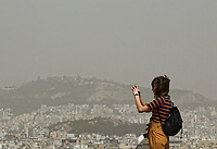 Pictured: People enjoy the view of Athens in Greece. Monday 26 March 2018<br /> Re: Strong southern winds from Africa have carried red dust over to Greece.