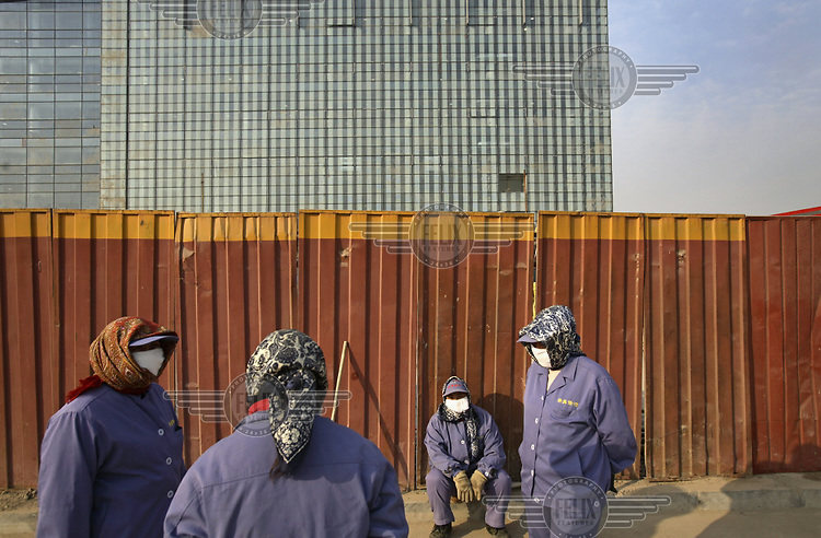 Female migrant workers, who clean the Olympic Games venues, during their break...