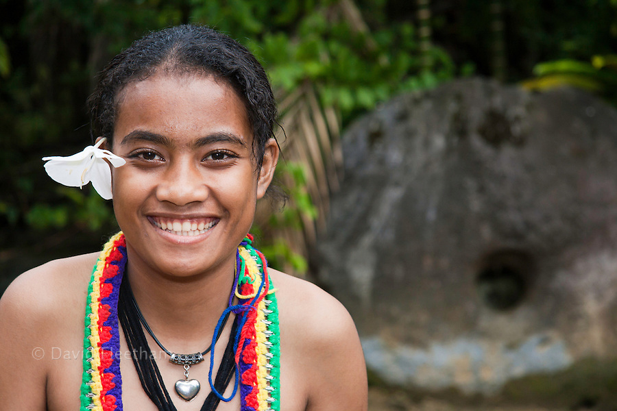 This young native girl is pictured in front of a piece of Yap's famous stone money in the village of Kadai, on the island of Yap, Micronesia.