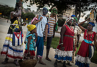 Havana, Cuba, sept 2014.People dressed fotr a religous event.             In recent years, Raul Castro has made several economic measures for the people of the island. Cubans can now buy and sell apartments or cars, can stay in hotels on the island and can travel abroad with minor difficulties. Most of the global economists believe that these changes are moving in the right direction but its positive effects on people are very slow. Cubans continue to struggle daily through the streets of Havana with humor and zest for life.                                  En los ultimos años Raul Castro ha realizado varias medidas economicas para el pueblo de la isla. Ahora los cubanos pueden comprar y vender departamentos o coches, pueden alojarse en hoteles de la isla y pueden viajar al extranjero con menores dificultades. La mayor parte de los economistas mundiales consideren que estos cambios se mueven en la justa direccion pero sus efectos positivos sobre la gente son muy lentos. Los cubanos siguen luchando a diario por las calles de La Habana con humorismo y ganas de vivir.