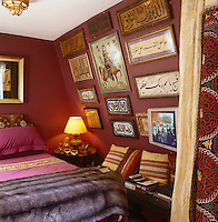 The sloping walls of the attic bedroom are decorated with a collection of framed Arabic calligraphy