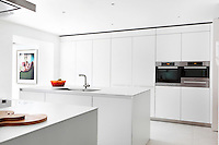 A modern stylish white kitchen with a sink set in a central island unit and integral ovens in the flush wall cabinets.