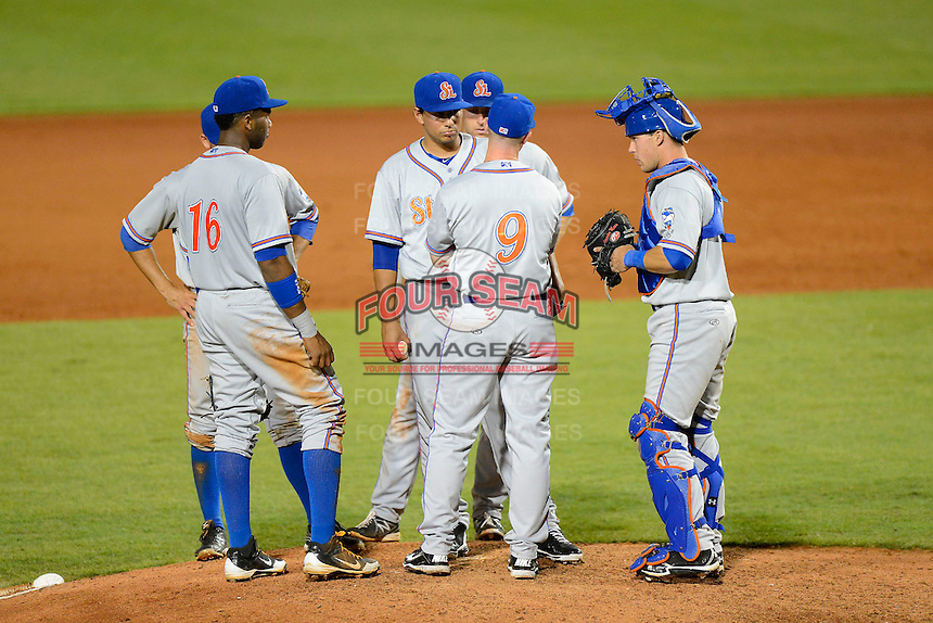 St. Lucie Mets manager Ryan Ellis #9 talks with pitcher Randy Fontanez as infielders Aderlin Rodriguez #16, catcher Cam Maron #7 listen in during a game against the Bradenton Marauders on April 12, 2013 at McKechnie Field in Bradenton, Florida.  St. Lucie defeated Bradenton 6-5 in 12 innings.  (Mike Janes/Four Seam Images)