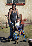Tarisayi Zhanje stands with her grandson, Hailey Kushaya, outside their home in Harare, Zimbabwe. She cares for the 9 year old since his parents died. At school he uses an appropriately-designed and fitted wheelchair provided by the Jairos Jiri Association with support from CBM-US.