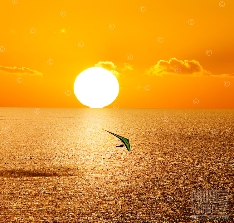 A hang glider soaring over the Pacific ocean near O'ahu at sunset.