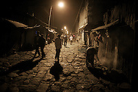"""Men walk through the area where commercial sex workers wait for their clients in the """"Merkato"""" neighborhood of Ethiopia's capital Addis Ababa on February 20, 2009 in Ethiopia..While in decline, early child marriage is still widely spread in rural areas of Ethiopia where families sell their daughters into marriage at ages as young as 5 years old...Names of subjects have been fictionalized and specific locations have been omitted to protect the identities of the children portrayed in the story."""