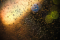 Raindrops against a window with the bokeh of lights behind it