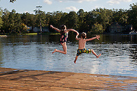 Little boy and girl jumping off a summertime dock and into a public lake