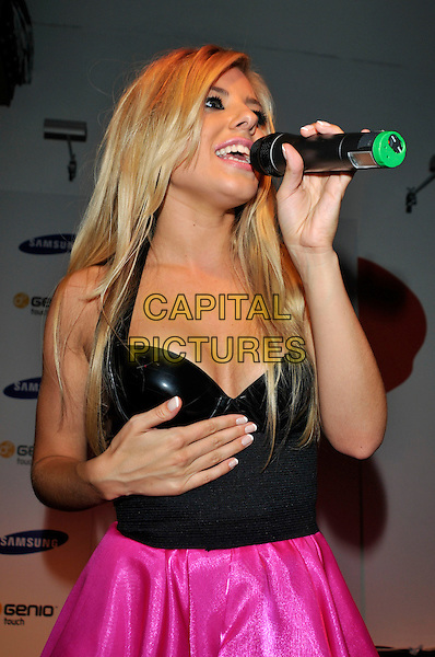 THE SATURDAYS - Mollie King .Launch of the new mobile phone Samsung Genio Touch at Proud Camden, London, England..September 14th, 2009.stage concert live gig performance music half pink skirt black strapless top pvc leather length singing hand cleavage.CAP/PL.©Phil Loftus/Capital Pictures.