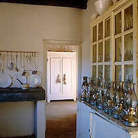View of the rustic kitchen and a row of well-used paraffin lamps lined up along the dresser