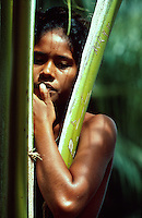 Environmental portrait of a young Micronesian woman and palm tree.
