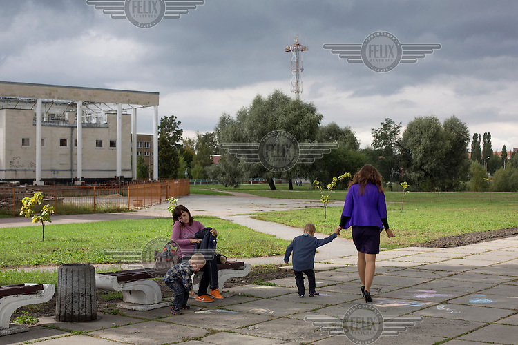 Two women with their sons in a park in Slavutich which lies near the exclusion zone around the site of the Chernobyl nuclear reactor disaster. Many of the people who work inside the exclusion zone live in this town.