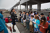 Job seekers from the countryside arrive on the edge of Chongqing city to apply for work at the Foxconn factory. <br /> <br /> The workers, mostly children of farmers, are part of a generation that is quickly urbanizing. <br /> <br /> They are being picked up at the light rail station for  interview at Apple's contract factory. If they succeed, they would land jobs making Apple products including the iPhone. <br /> <br /> Foxconn hit the news last year when it was rocked by a series of workers' suicide. <br /> <br /> China is pushing ahead with a dramatic, history-making plan to move 100 million rural residents into towns and cities between 2014 and 2020 &mdash; but without a clear idea of how to pay for the gargantuan undertaking or whether the farmers involved want to move.<br /> <br /> Moving farmers to urban areas is touted as a way of changing China&rsquo;s economic structure, with growth based on domestic demand for products instead of exporting them. In theory, new urbanites mean vast new opportunities for construction firms, public transportation, utilities and appliance makers, and a break from the cycle of farmers consuming only what they produce.<br /> <br /> Urbanization has already proven to be one of the most wrenching changes in China&rsquo;s 35 years of economic reforms. Land disputes rising from urbanization account for tens of thousands of protests each year.