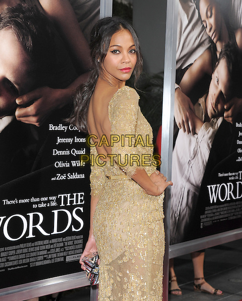 "Zoe Saldana.""The Words"" Los Angeles Premiere held at Arclight Cinemas, Hollywood, California, USA..September 4th, 2012.half length gold lace beads beaded dress belt hand on hip backless looking over shoulder .CAP/RKE/DVS.©DVS/RockinExposures/Capital Pictures."