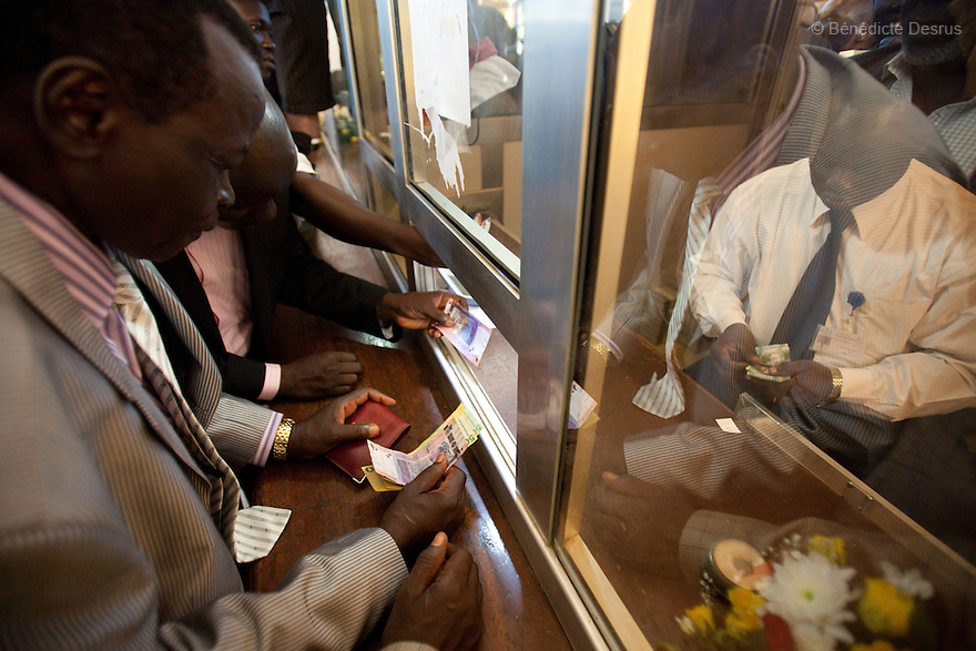 July 18, 2011 - Juba, Republic of South Sudan - First South Sudanese citizens to change their money at the Central Bank. Newly independent South Sudan distributes it's new currency at the Central Bank of South Sudan. The new South Sudanese Pounds are exchanged for for Sudanese Pounds (SDG) at a rate of 1:1. The new currency carries images of South Sudan's civil war hero John Garang on one side and South Sudanese scenes on the other side. The South Sudanese pound is printed in denominations of one, five, ten, twenty-five, fifty and one hundred. South Sudan became the world's newest country when it seceded from the north on Saturday 9 july 2011, following decades of civil war that left millions dead. The new nation was also formally accepted as a Member State of the United Nations. Photo credit: Benedicte Desrus