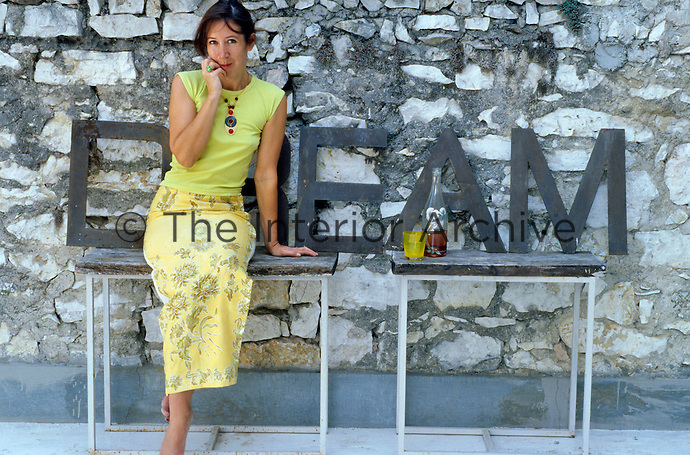 Designer Carolyn Quartermaine sits on a makeshift bench against a stone wall