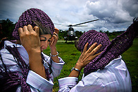 'Twin Teachers' Rian and Rossy hold on to their hats as they prepare to hitch a ride from a Super Puma military helicopter to go to a remote village in Indonesia's Papua province to visit students from one of their schools. Since the early 1990s, twin sisters Sri Rosyati (known as Rossy) and Sri Irianingsih (known as Rian) have used their family inheritance to set up and run 64 schools in different parts of Indonesia, providing primary education combined with practical skills to some of the country's most deprived children.