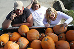 Toby Ogans, Jennifer Ogans and Kristen Curtis choose which pumpkins to take home with them in front of G&T Grocery on Thursday, September 30, 2010.  .Photo by Latara Appleby