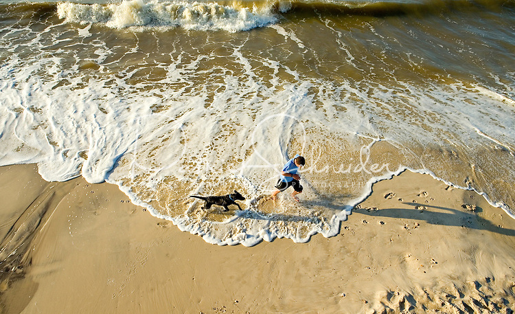 A teenage boy and his black lab dog run along the beach on Dauphin Island, Alabama, a barrier island located three miles south of the mouth of Mobile Bay in the Gulf of Mexico. This island, which is approximately 14 miles long and less than two miles wide, appears to have fully recovered from the impact of Hurricane Katrina (2005) and the BP Deepwater Horizon Oil Spill in 2010. Both events greatly reduced tourism income (fewer people came to the island) and local business owners say many establishments went out of business. Today they say they're looking forward to a rebounding tourism business.