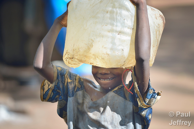 A girl carries water in a camp for for than 5,000 displaced people in Riimenze, in South Sudan's Gbudwe State, what was formerly Western Equatoria. Families here were displaced at the beginning of 2017, as fighting between government soldiers and rebels escalated.<br /> <br /> Two Catholic groups, Caritas Austria and Solidarity with South Sudan, have played key roles in assuring that the displaced families here have food, shelter and water.