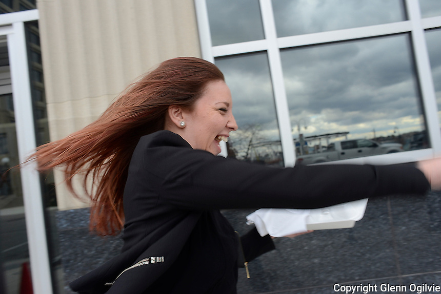 Rachel Grondin, a worker for Norton's Hairstyling battles strong November winds while fetching a bite from a local Front Street eatery.