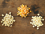 Cubes of colby, pepper jack, and white cheddar on a wooden table with peppers and crackers