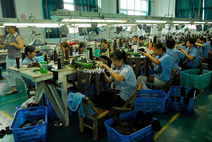 "Workers at the Shuangshuang Sock Company in ""Datang Sock Town"" in Zhuji City Zhejiang Province, China. The town in Zhejiang Province makes more than 5.3 billion pairs of socks annually - that 2.5 pairs for every human alive..14 Jun 2006"