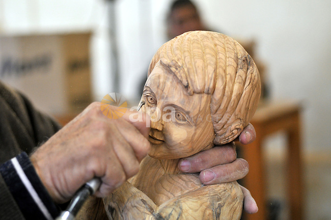A Palestinian carpenter carves a wooden sculpture of baby Jesus at a workshop in the West Bank town of Bethlehem, on December 20, 2012. The traditional birthplace of Jesus Christ prepares to celebrate Christmas later this month. Photo by Issam Rimawi