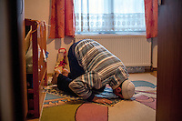 Elvis Causevic praying at home. <br /> <br /> In 1992 while volunteering at the Varazdin refugee camp Panos photographer Bjoern Steinz met and became close to Elvis, a Bosnian Muslim refugee, and his family. They shared the hardships of camp life together which Steinz documented. While the prints were archived for many years two of the images always returned to Bjoern's thoughts. 25 years later he set out to try and find out what had happened to Elvis and his family in the intervening years. Modern social media made the task surprisingly easy and they were reunited in Hadzici where Elvis now lives with his family.