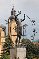 Multicultural Man, bronze sculpture by Francesco Perilli of a man surrounded by doves, given by the Italian people to Sarajevo citizens in 1997, and behind, the Cathedral Church of the Nativity of the Theotokos, built 1863-68 by Andreja Damjanov during the Ottoman empire, with its separate belfry in front, Sarajevo, Bosnia and Herzegovina. The sculpture is one of a series in several cities around the world. Picture by Manuel Cohen