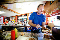 H&M Hot Dog owner Dan Pinson covers a dog. Pinson said his eatery is Florida's oldest continuously operating hot dog stand..COLIN HACKLEY PHOTO