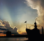 Shafts of sunlight and smoke from industrial chimney with the silhouette of a warship in the foreground. Ft Lauderdale harbour. Florida, Unites States.  November 1976