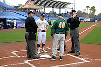 Michigan Wolverines head coach Erik Bakich (23) talks with Tony Rossi (4) and umpires Dorsey Hager (left), Robert Lothian (right) and Mark Spicerduring (hidden) before the second game of a doubleheader against the Siena Saints on February 27, 2015 at Tradition Field in St. Lucie, Florida.  Michigan defeated Siena 6-0.  (Mike Janes/Four Seam Images)