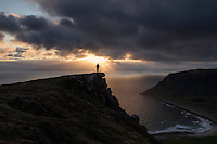 Female hiker watches midnight sun over sea from Nonstind mountain peak, Vestvågøy, Lofoten Islands, Norway