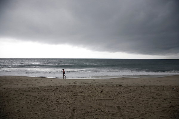 A woman walks along the beach in Cape May before a rainstorm from Tropical Storm Danny.