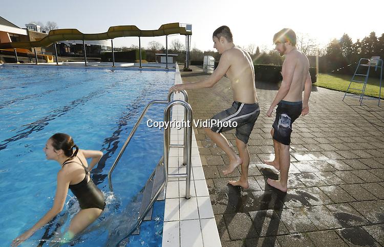 Foto: VidiPhoto<br /> <br /> NIJMEGEN - Ondanks dat het winter is, gooit het Sportfondsenbad Nijmegen-West toch het buitenbad open. Vanaf dinsdag tot en met 2 januari kunnen bezoekers ook buitenzwemmen. De technische dienst van het zwembad kwam op dat idee omdat er in de winter door gebruik van warmtekrachtkoppeling (WKK) warmte over is. Normaal gesproken wordt dat in de lucht geblazen, maar nu wordt dat gebruikt om het buitenbad te verwarmen. De temperatuur van het buitenbad is daardoor zo'n 20 graden. Doordat de buitentemperatuur zo'n 7 graden Celcius is, voelt dat redelijk aangenaam aan. Om bevriezing van de tegels te voorkomen, staat er ook 's winters water in het bad. Er hoeven daarom geen extra kosten gemaakt te worden. De belangstelling voor het buitenzwemmen is boven verwachting. Om te zwemmers wat te verwarmen zijn er enkele vuurkorven geplaatst.