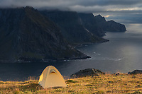 Wild mountain camping on summit of Fuglhuken mountain peak with rugged northern coast of Moskenesøy in background, Lofoten Islands, Norway