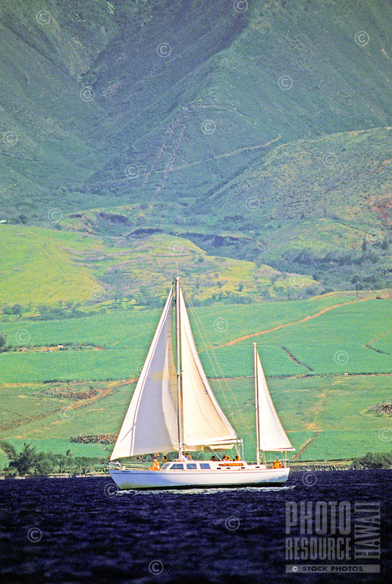 A beautiful white sailboat is poised against the distinctive green West Maui mountains.