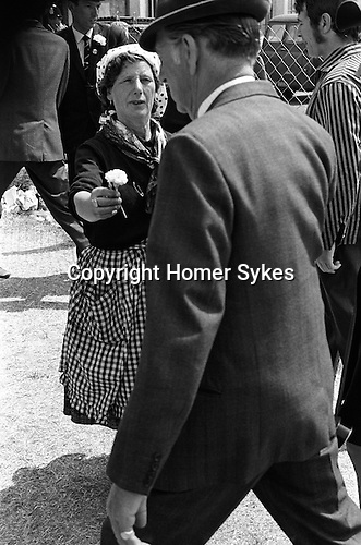 Gypsy Roma  woman selling good luck carnation flowers to race goers. Derby Day horse race. Epsom Down Surrey England.  1970