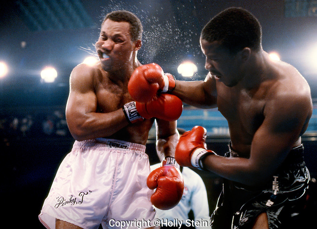 Tim Witherspoon delivers a right to Pinklon Thomas during their WBC heavyweight title fight.  Thomas won by a majority decision, 12 rds.