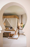 ZANZIBAR, a gold and white canopy bed in the Baraza Hotel, seen through an arch