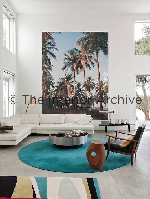 An inspiring, open plan living space with a double height ceiling. A large picture of Goa hangs on the wall behind a white sofa from B&B Italia. A Willy Rizzo coffee table, a Nordic retro armchair and a brazil wood trunk carving stand on a vibrant turquoise carpet by Carpet Diem.
