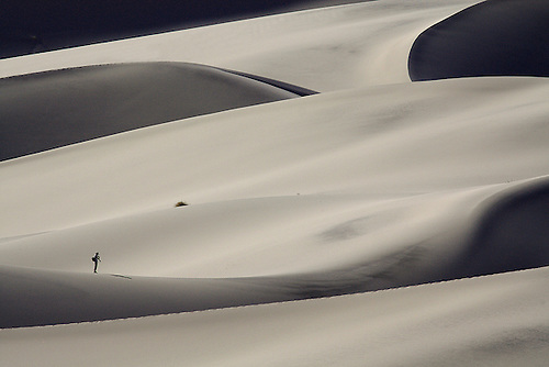 A HIKER ATTEMPTS TO CLIMB UP THE STEEP SLOPES OF EUREKA SAND DUNES IN DEATH VALLEY NATIONAL PARK,CALIFORNIA