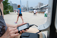 Cellphone and tablet users take advantage of a solar powered charging station in Brooklyn Bridge Park in New York on their first day of operation, Tuesday, June 18, 2013. The stations, provided by AT&T in a pilot program, allow New Yorkers and visitors to charge their devices, up to six at each station. Twenty-five stations are planned in public parks as part of the program being left at the various locations three to four weeks at a time. They will be placed in parks such at Union Square, Fort Greene, Hudson River and on Coney Island and Rockaway Beach among other locations. A smartphone can be charged in two hours or a 30 percent charge in 30 minutes. (© Richard B. Levine)