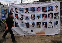 """MEDELLÍN - COLOMBIA, 07-06-2014. Una mujer pasa frente a las fotos con los nombres de las personas desaparecidas en """"La Escombrera"""", en la Comuna 13 de Medellín, durante una vigilia contra las desapariciones forzadas. En 2002, Medellín fue sacudido por la violencia después de la decisión del Gobierno de recuperar un sector de la ciudad disputada por los paramilitares de derecha y las milicias de izquierda. Según los familiares de las víctimas, en la operación ordenada el 16 de octubre de 2002 por el presidente Álvaro Uribe, decenas de personas murieron, más de 100 personas resultaron heridas, 98 personas desaparecieron y más de 200 familias fueron desplazadas./  A woman walks in front of the images with the names of missing persons in """"La Escombrera"""" in Comuna 13 in Medellín, during a vigil against forced disappearances. In 2002, Medellín was rocked by violence following the government's decision to recover a part of the city disputed by right-wing paramilitaries and leftist militias. According to relatives of the victims, the orderly operation on October 16, 2002 by President Alvaro Uribe, dozens of people were killed, over 100 people were injured, 98 people missing and more than 200 families were displaced. Photo: VizzorImage/Luis Rios/STR"""
