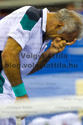 Mansour Bahrami from Iran wipes sweat from his forehead during an exhibition duo match together with Fernando Verdasco (not pictured) from Spain against Gael Monfils (not pictured) and Fabrice Santoro (not pictured) from France during the Tennis Classics tournament in Budapest, Hungary on October 29, 2011. ATTILA VOLGYI