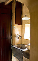 An ancient stone wash basin is situated in an alcove beneath a small window