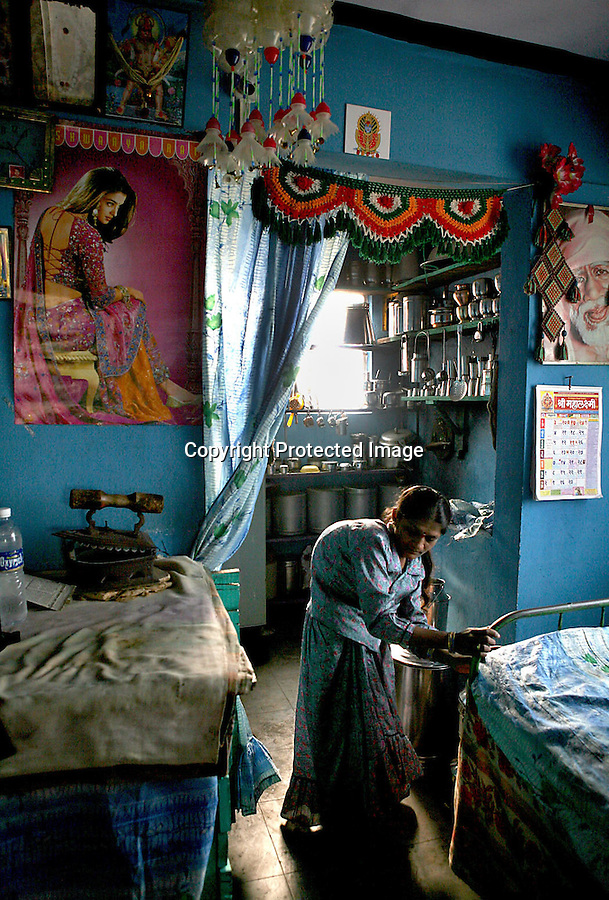 Jaya Kamble, 24, uses the bed frame for support as she walks around her home in Sangli, India, where she lives with her sister and mother in a government housing project.  Looking down from the wall is famed Bollywood actress, Aishwarya Rai Bachchan.