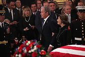 Former President George W. Bush walks past the casket with his wife former first lady Laura Bush during services for his father former President George H.W. Bush in the U.S. Capitol Rotunda in Washington, U.S., December 3, 2018. REUTERS/Jonathan Ernst/Pool
